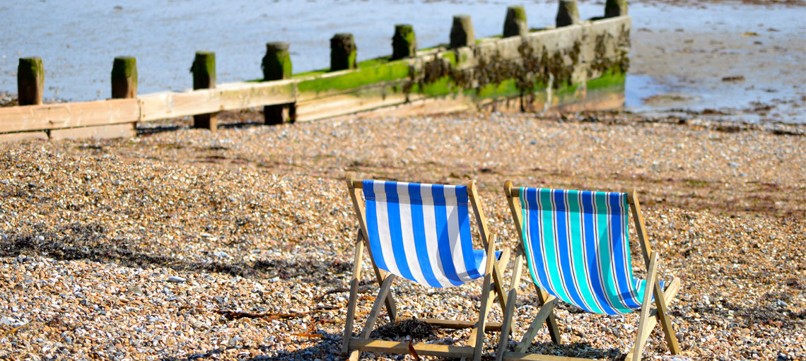 Deckchairs on pebble beach.